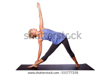 Beautiful healthy woman doing Triangle Utthita Trikonasana yoga pose standing on mat, on white. - stock photo