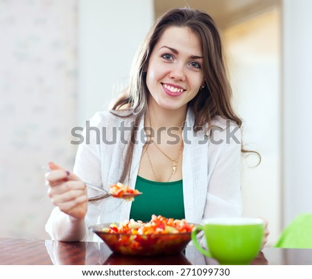 beautiful healthy woman eating veggie salad with spoon at home - stock photo
