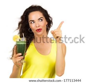 Beautiful healthy woman holding an organic green smoothie and pointing at copy-space.  Isolated on white. - stock photo