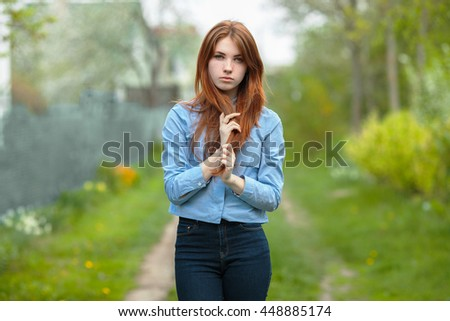Beautiful healthy young redhead woman touch her hair posing on the green grass of country road