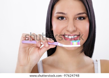 Beautiful healthy young woman Brushing her teeth - stock photo