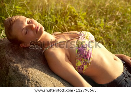 Beautiful healthy young woman relaxing on the stone