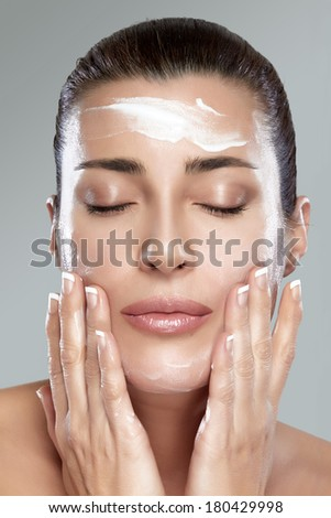 Beautiful healthy young woman with eyes closed while applying moisturizer to her clean face using gentle soft touches, close-up portrait on grey. Perfect skin. Skincare concept. - stock photo