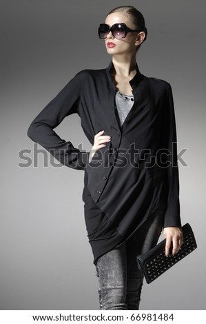 Beautiful high fashion model in modern clothes hold purse posing - stock photo