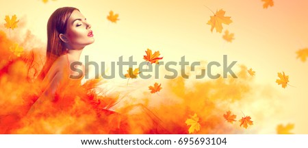 Beautiful High fashion woman in autumn yellow dress with falling leaves over yellow background. Gorgeous brunette model girl, beautiful make-up, Wearing Stunning evening dress with long gown of tulle