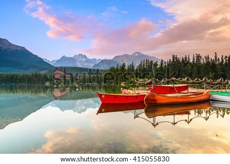Beautiful high mountains around the incredibly magic lake with red boats and canoe on a spring day. Strbske Pleso lake, Slovakia, Tatra mountains. - stock photo