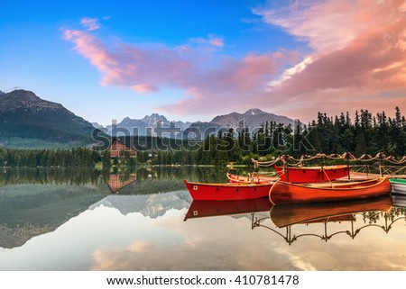 Beautiful high mountains around the incredibly magic lake with red boats on a spring day. Strbske Pleso lake, Slovakia, Tatra mountains. - stock photo