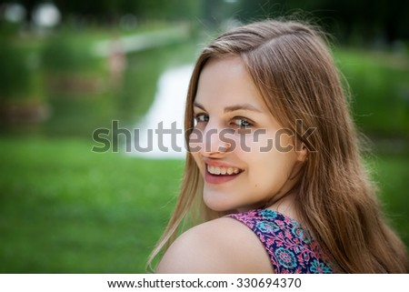 Beautiful high school senior girl portrait looking over shoulder smiling outside at a park - stock photo