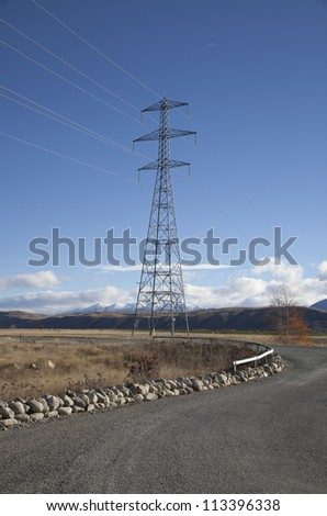 Beautiful high voltage electric pole across the land against the blue sky and clouds in New Zealand