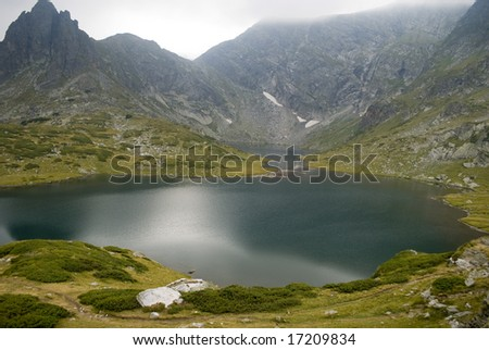 Beautiful highland lake and vast mountain on a cloudy day. The picture was taken on the Seven Rila lakes (above 2200m.) in Rila mountain, Bulgaria.