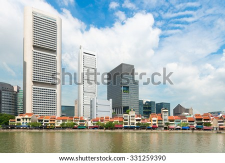 Beautiful, highrise buildings of contemporary architectural design, towering over smaller buildings and an old, concrete boat quay along the water's edge in Singapore. - stock photo