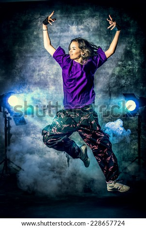 Beautiful hip-hop dancer jumping over grunge background. - stock photo