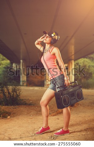 Beautiful hip hop woman with a tape recorder and headphones enjoying the music - stock photo