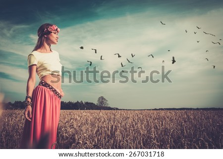 Beautiful hippie girl in a field - stock photo