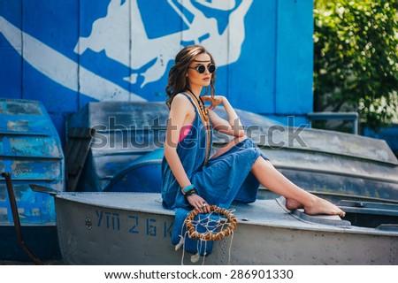 beautiful hippie girl posing near the boat - stock photo