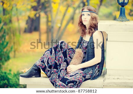 Beautiful hippie girl sitting in autumn scenery wearing maxi long dress and gorgeous make up.