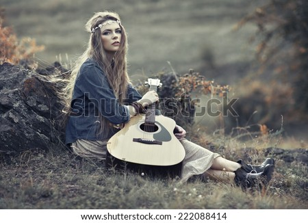 Beautiful hippie girl with guitar sitting on field near stone - stock photo