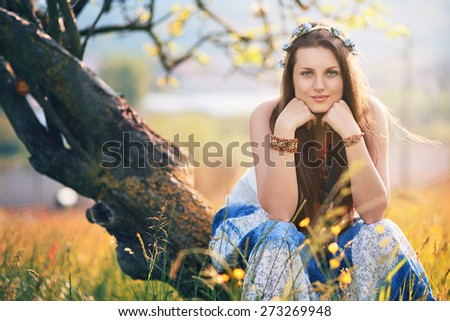Beautiful hippie woman posing in a summer field. Peace and harmony - stock photo
