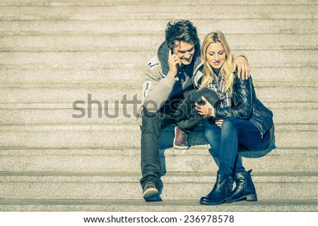 Beautiful hipster couple in love having a smartphone call - Modern concept of connection in a relationship together with mobile phone technology - City stairs urban lifestyle and everyday life rapport - stock photo