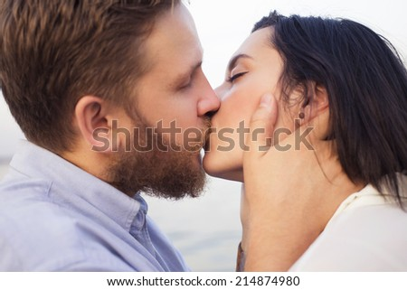Beautiful hipster couple in love on a date outdoors in park having fun. Bearded red hair man. Brunette woman in black skirt and white blouse. Near river sea