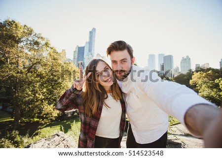 Beautiful hipster couple taking selfie photo in Central Park, New York. Young and funny students take photo for travel blog.