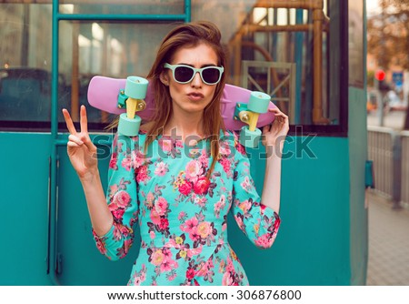 Beautiful hipster fashion young woman model posing with a pink skateboard on city background in vogue sunglasses - stock photo