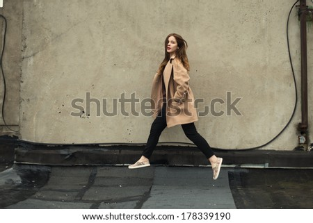 beautiful hipster girl in coat jumping - stock photo