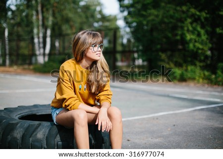 Beautiful hipster girl sitting on the wheel of the truck - stock photo