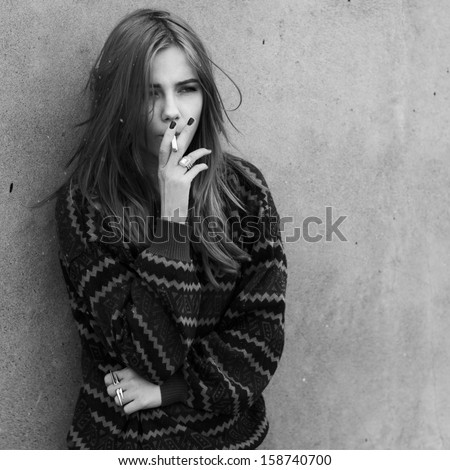 beautiful hipster girl smokes outdoors - stock photo