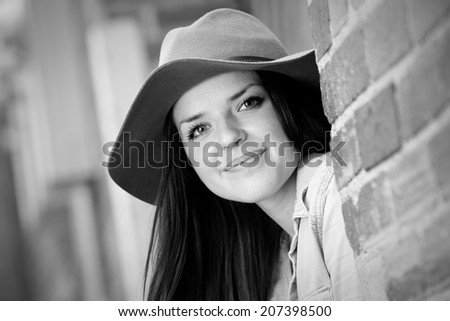 Beautiful Hipster Girl - This is a black and white shot of a beautiful young woman sitting in an urban alleyway with a hat and smiling. Shot with a shallow depth of field.