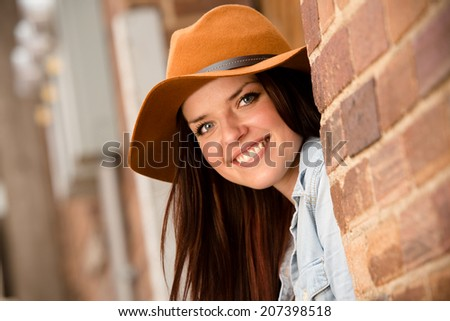 Beautiful Hipster Girl - This is a shot of a beautiful young woman sitting in an urban alleyway with a hat and smiling. Shot with a shallow depth of field. - stock photo