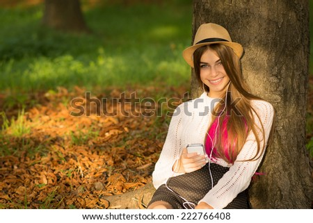 Beautiful hipster girl with long blonde and pink dyed hair and hat holding smartphone sitting in park in autumn smiling. Closeup of teenage girl using smart phone. No retouch. - stock photo