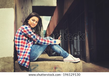 Beautiful hipster mixed race teenage girl sitting in urban environment with smart phone and headphones looking at camera. Contemporary lifestyle concept. - stock photo