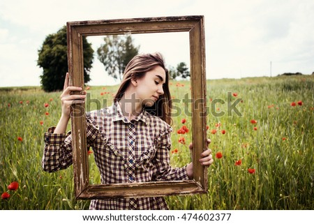 Beautiful hipster woman in retro stylish dress posing with picture frame in poppies field