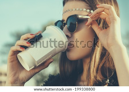 Beautiful hipster woman in sunglasses drink  coffee. Close-up lifestyle outdoor portrait - stock photo