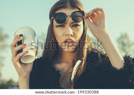 Beautiful hipster woman in sunglasses with cup of coffee - stock photo