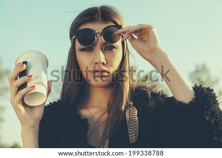 Beautiful hipster woman in sunglasses with cup of coffee. Close-up lifestyle outdoor portrait - stock photo