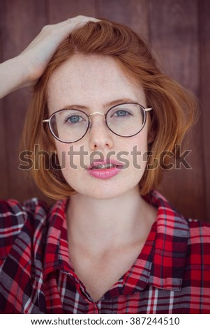 beautiful hipster woman staring into the camera against a wooden background - stock photo