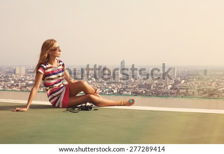 Beautiful hipster woman with small photo camera sitting on the roof of skyscraper in sity  travel - stock photo