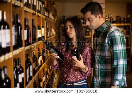 Beautiful Hispanic couple choosing a bottle of wine in a wine cellar - stock photo