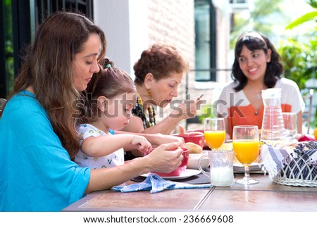 Beautiful hispanic family with a girl toddler having breakfast together on the outdoor dining showing family bonding time. - stock photo