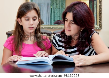 Beautiful hispanic girl and her young mother reading a book together or studying at home - stock photo