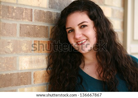 beautiful hispanic girl with long curly hair smiling