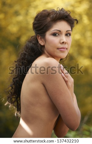 Beautiful Hispanic model standing in front of vivid yellow tree on sunny day.