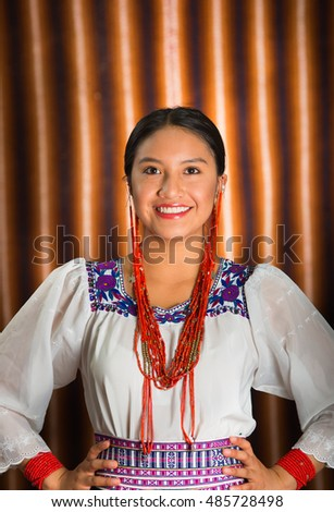Beautiful hispanic model wearing andean traditional clothing smiling and posing for camera, beige studio curtain background