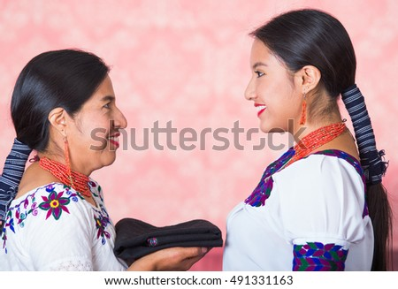 Beautiful hispanic mother and daughter wearing traditional andean clothing, seen from profile angle facing each other holding blanket between them, pink studio background