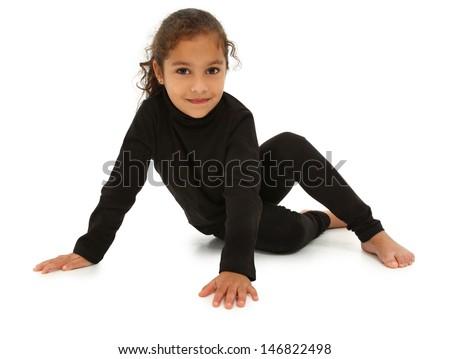 Beautiful hispanic preschool girl sitting on white floor with clipping path. - stock photo