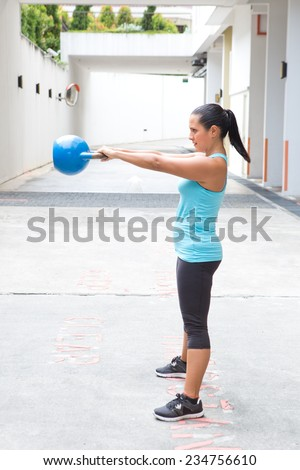 Beautiful hispanic sport woman swing the blue kettlebell, outdoor - stock photo
