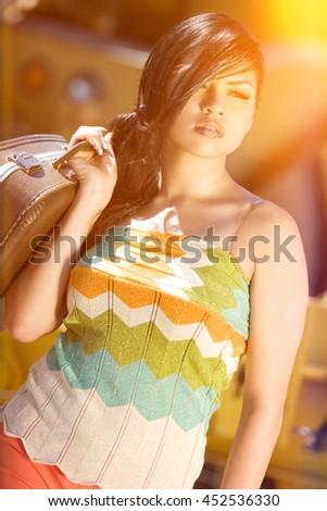 Beautiful hispanic woman carrying suitcase - stock photo