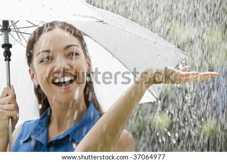 Beautiful Hispanic woman holding umbrella out in the rain - stock photo